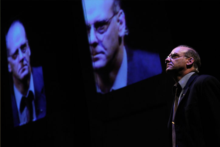 """Re:Union,"" an original play be Sean Devine, produced by Horseshoes and Handgrenades Theatre in Vancouver, 2011. It included a striking use of projection, which included still images and multiple images of the same live feed. Pictured here is Andrew Wheeler, who played Robert McNamara. Jason H. Thompson. Projection; John Webber, Set and Lights; Flo Barrett, Costumes; John Langs, Director. Photo by Ron Reed."